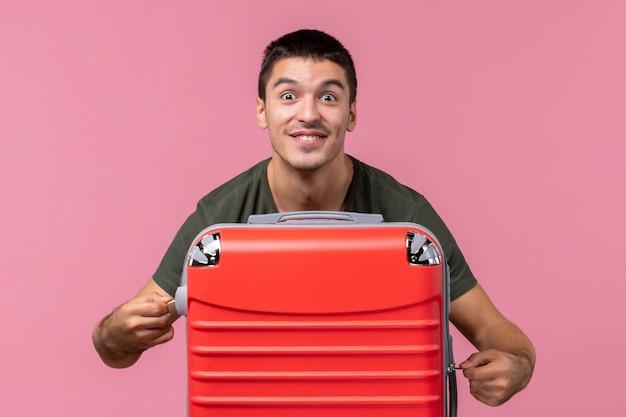 Vooraanzicht jonge man bereidt zich voor op vakantie en sluit zijn tas op roze ruimte