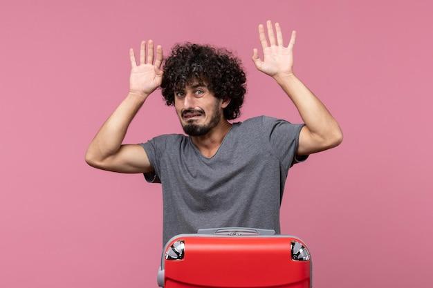 Vooraanzicht jonge man bereidt zich voor op vakantie en voelt zich bang op roze ruimte