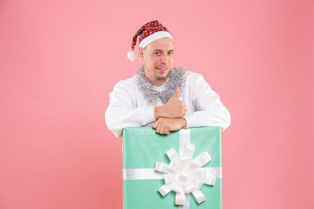 Vooraanzicht jonge man binnen aanwezig lachend op roze achtergrond