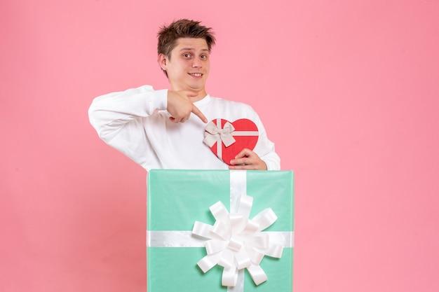 Vooraanzicht jonge man binnen aanwezig met cadeau op roze achtergrond