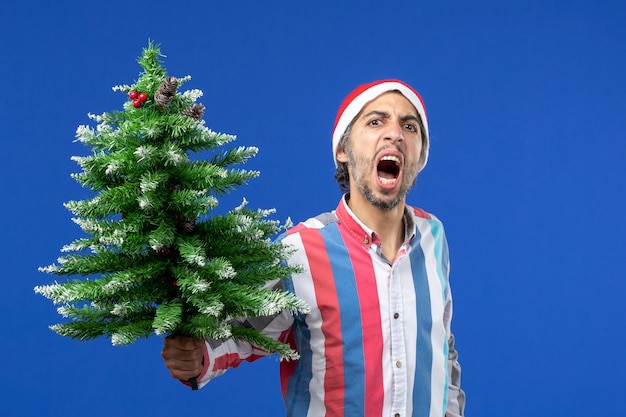 Vooraanzicht jonge man boos met nieuwe jaarboom op blauwe muur nieuwe jaar emotie vakantie
