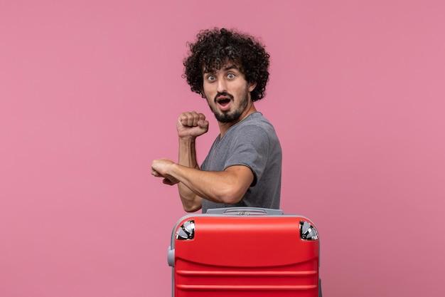 Vooraanzicht jonge man die de tijd controleert met een verbaasde uitdrukking op roze ruimte