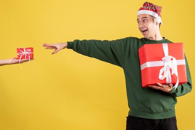 Vooraanzicht jonge man die het geschenk in vrouwelijke hand probeert te vangen die zich op geel bevindt