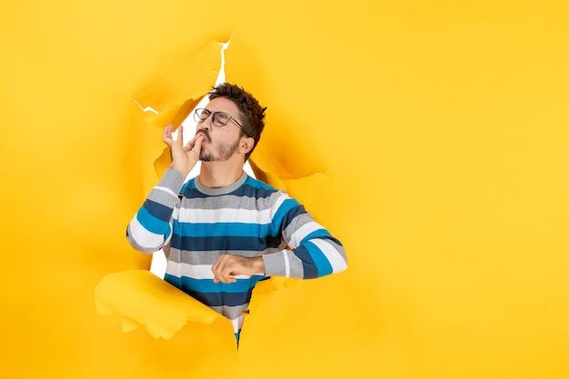 Vooraanzicht jonge man die hoofdkus maakt en door een gat in de gele muur van papier gluurt