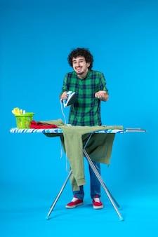 Vooraanzicht jonge man die ijzer op de blauwe achtergrond probeert te repareren mens schone wasmachine huishoudelijk werk kleur huis