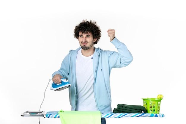 Vooraanzicht jonge man die ijzer vasthoudt terwijl hij zich boos voelt op een witte achtergrond ijzer kleur man wasgoed kleren huishoudelijk werk schoonmaken emotie