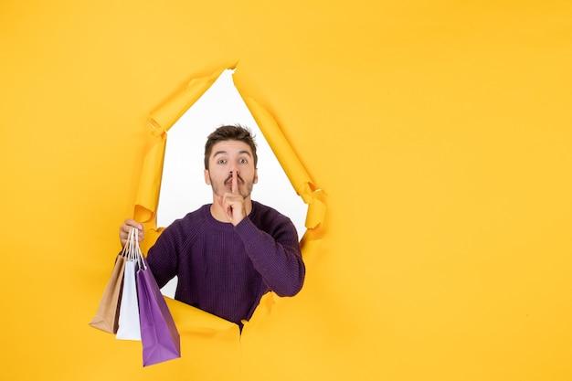 Vooraanzicht jonge man die kleine pakjes vasthoudt na het winkelen op een gele achtergrond cadeau nieuwjaar aanwezig xmas kleur vakantie