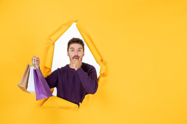 Vooraanzicht jonge man die kleine pakjes vasthoudt na het winkelen op gele achtergrond cadeau nieuwjaar cadeau kleur vakantie