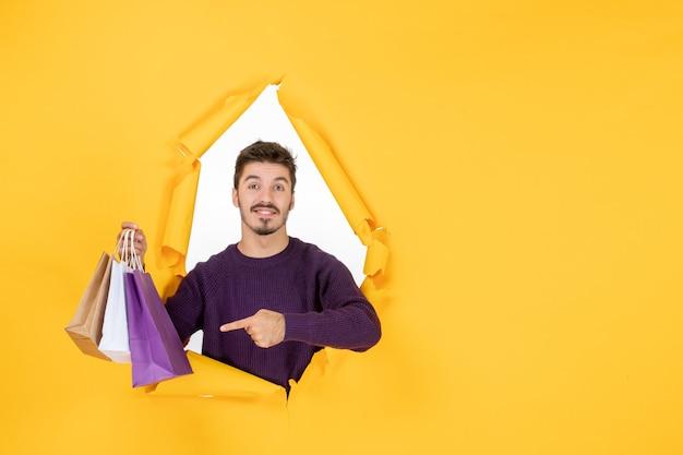 Vooraanzicht jonge man die kleine pakjes vasthoudt na het winkelen op gele achtergrond model cadeau nieuwjaar aanwezig xmas kleur