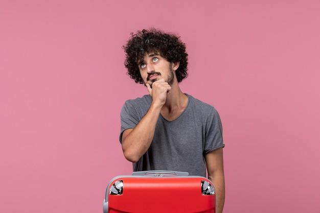 Vooraanzicht jonge man die op vakantie gaat met zijn rode tas denkend aan roze ruimte