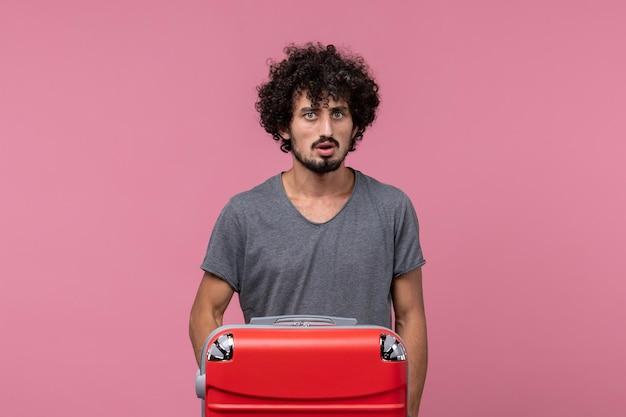 Vooraanzicht jonge man die op vakantie gaat met zijn rode tas op de roze ruimte