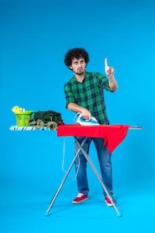 Vooraanzicht jonge man die rode kleren aan boord strijkt op blauwe achtergrond kleur huis wasmachine huishoudelijk werk mens