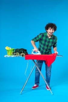 Vooraanzicht jonge man die rode kleren aan boord strijkt op blauwe achtergrond kleur huis wasmachine huishoudelijk werk menselijk schoon