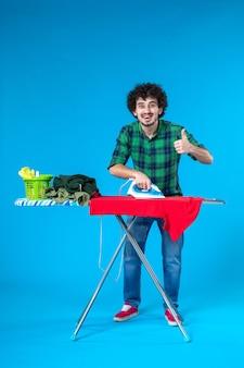 Vooraanzicht jonge man die rode kleren aan boord strijkt op blauwe achtergrond kleur huis wasmachine menselijk schoon