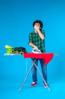 Vooraanzicht jonge man die rode kleren aan boord strijkt op de blauwe achtergrond kleur wasmachine huishoudelijk werk menselijk schoon huis