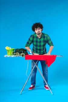 Vooraanzicht jonge man die rood overhemd aan boord op de blauwe achtergrond strijkt mens wasmachine huishoudelijk werk schoon huis kleur