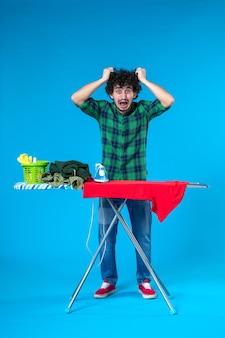 Vooraanzicht jonge man die rood overhemd aan boord strijkt en zijn haar scheurt op blauwe achtergrond menselijke wasmachine huishoudelijk werk schone huiskleur