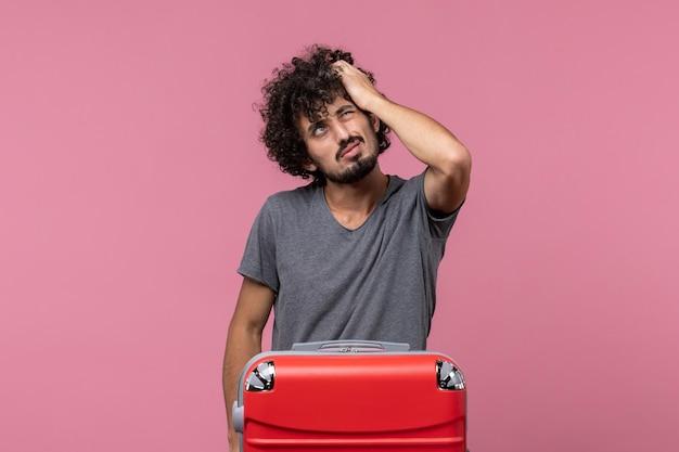 Vooraanzicht jonge man die zich klaarmaakt voor vakantie en aan roze ruimte denkt