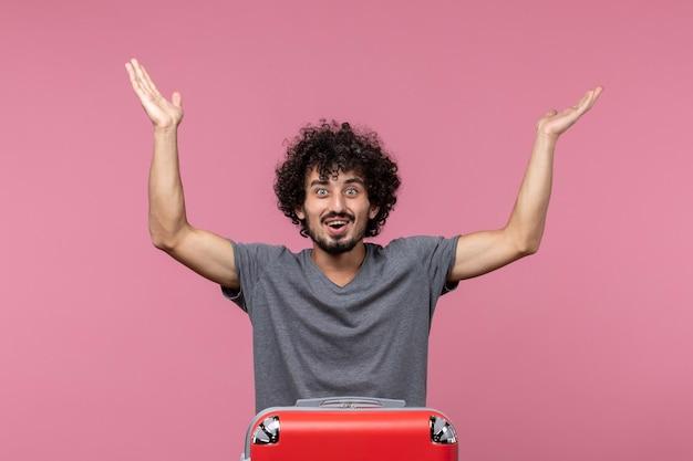 Vooraanzicht jonge man die zich klaarmaakt voor vakantie en zich gelukkig voelt op roze ruimte