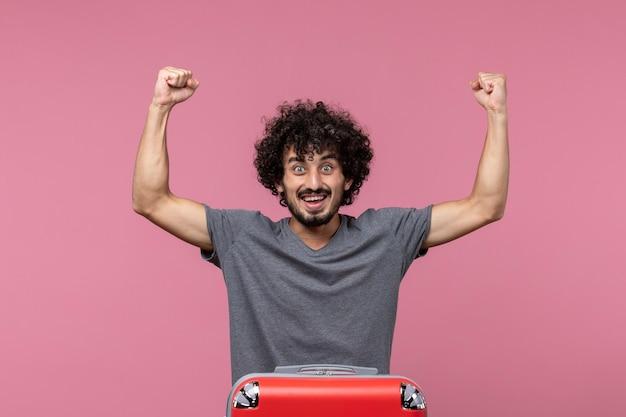 Vooraanzicht jonge man die zich klaarmaakt voor vakantie en zich verheugt op roze ruimte