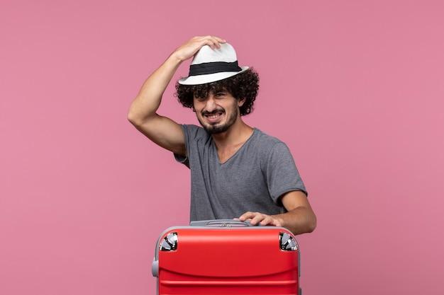 Vooraanzicht jonge man die zich voorbereidt op een reis en een hoed draagt op de roze ruimte