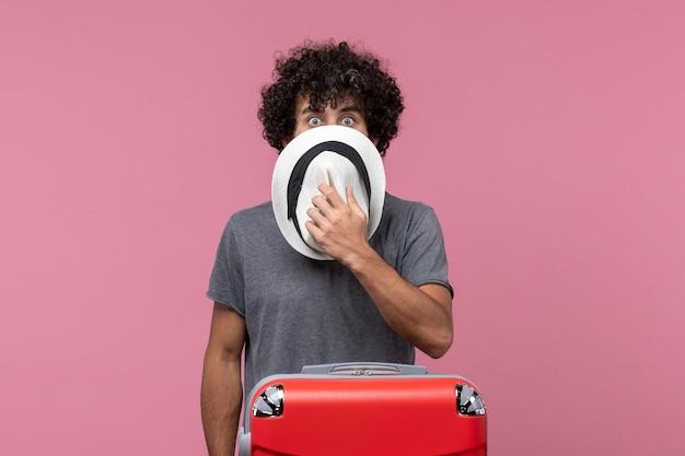 Vooraanzicht jonge man die zich voorbereidt op een reis en hoed op de roze ruimte houdt
