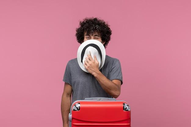 Vooraanzicht jonge man die zich voorbereidt op een reis en hoed op de roze ruimte houdt Gratis Foto