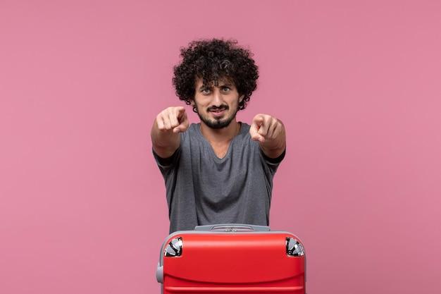Vooraanzicht jonge man die zich voorbereidt op een reis en wijst op roze ruimte
