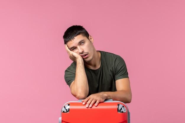 Vooraanzicht jonge man die zich voorbereidt op een reis en zich moe voelt op de roze ruimte
