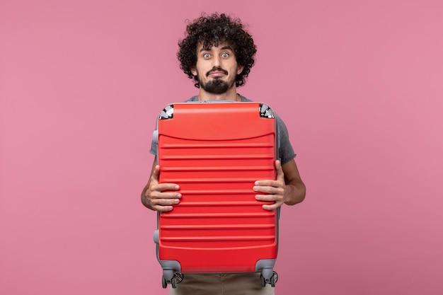 Vooraanzicht jonge man die zich voorbereidt op een reis en zijn tas op roze ruimte draagt