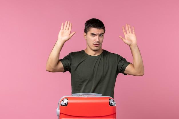 Vooraanzicht jonge man die zich voorbereidt op een reis met rode tas op roze ruimte