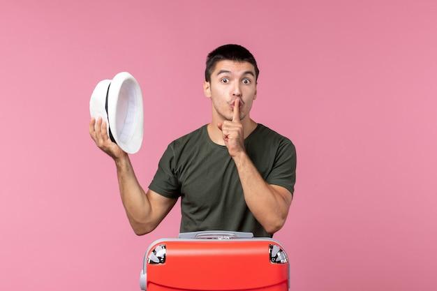 Vooraanzicht jonge man die zich voorbereidt op een vakantie met hoed op de roze ruimte