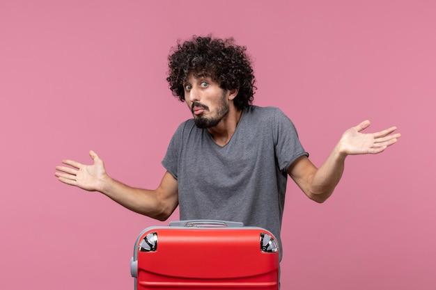 Vooraanzicht jonge man die zich voorbereidt op een vliegtuigreis op de roze ruimte