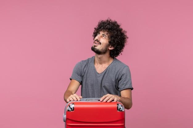 Vooraanzicht jonge man die zich voorbereidt op een vliegtuigreis op roze bureau