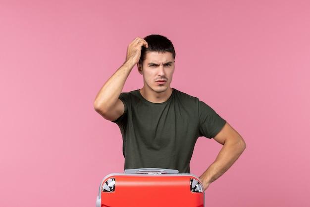 Vooraanzicht jonge man die zich voorbereidt op vakantie en denkt aan de roze ruimte