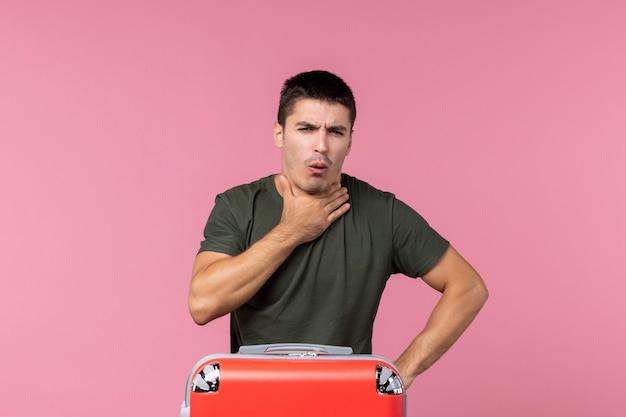 Vooraanzicht jonge man die zich voorbereidt op vakantie en hoest op roze ruimte