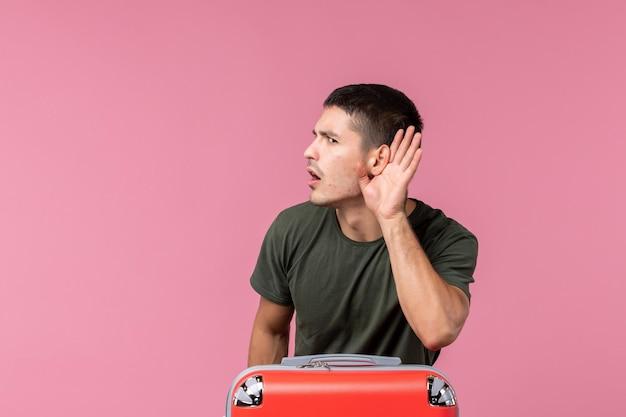 Vooraanzicht jonge man die zich voorbereidt op vakantie en nauw luistert op roze ruimte