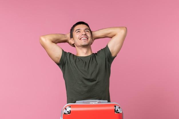Vooraanzicht jonge man die zich voorbereidt op vakantie en zich gelukkig voelt op de roze ruimte