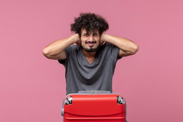 Vooraanzicht jonge man die zich voorbereidt op vakantie en zijn oren sluit op roze ruimte