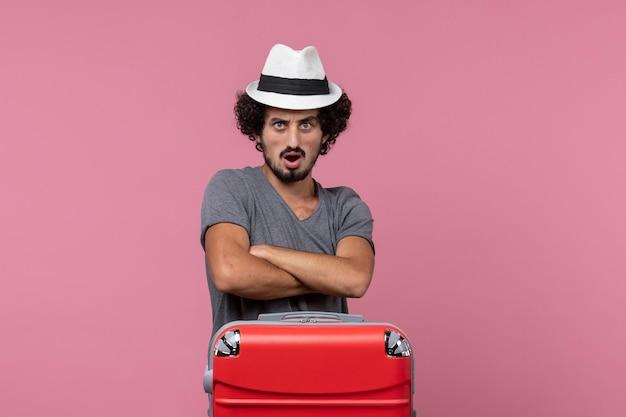 Vooraanzicht jonge man die zich voorbereidt op vakantie in hoed op de roze ruimte