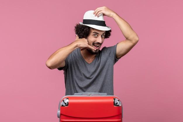 Vooraanzicht jonge man die zich voorbereidt op vakantie in hoed op lichtroze ruimte