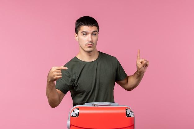 Vooraanzicht jonge man die zich voorbereidt op vakantie met grote tas op de roze ruimte