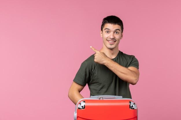 Vooraanzicht jonge man die zich voorbereidt op vakantie met grote tas op lichtroze ruimte