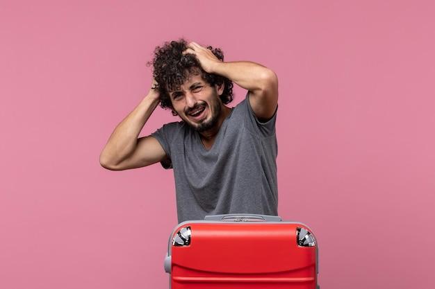 Vooraanzicht jonge man die zich voorbereidt op vakantie op de roze ruimte