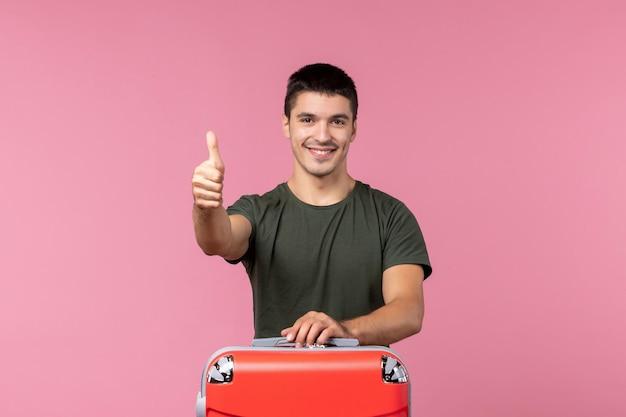 Vooraanzicht jonge man die zich voorbereidt op vakantie op lichtroze ruimte
