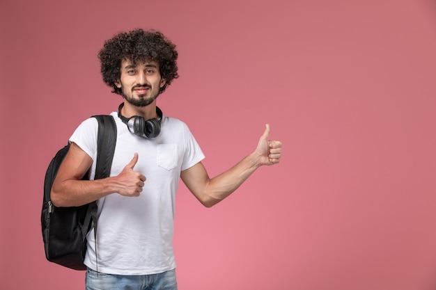 Vooraanzicht jonge man doet twee duimen omhoog met tas