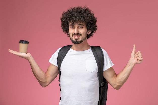 Vooraanzicht jonge man duimen opgevend en papier koffiekopje te houden