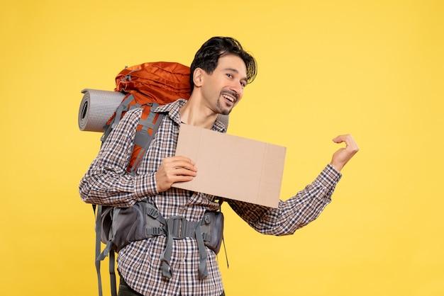 Vooraanzicht jonge man gaan wandelen met rugzak op geel