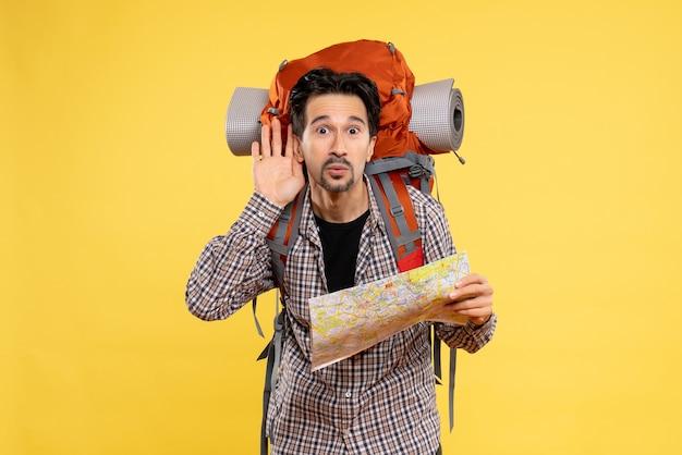 Vooraanzicht jonge man gaat wandelen met rugzak met kaart op gele achtergrond reis lucht natuur bedrijf campus bos kleur