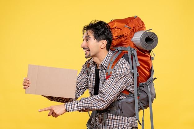 Vooraanzicht jonge man gaat wandelen met rugzak op de gele achtergrond kaart kleur natuur bedrijf bos reis campus lucht